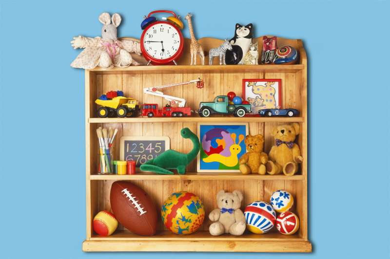 Wooden bookcase stacked with toys including rubber balls, cuddly animals and plastic cars and trucks.