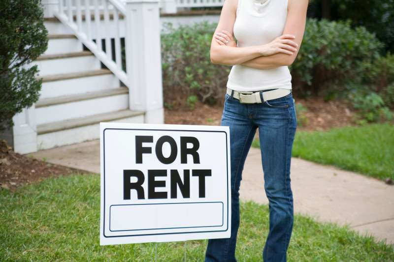 A young woman standing behind a ?for rent? sign