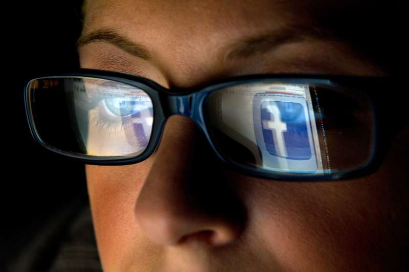 Woman with Facebook logo reflecting in glasses