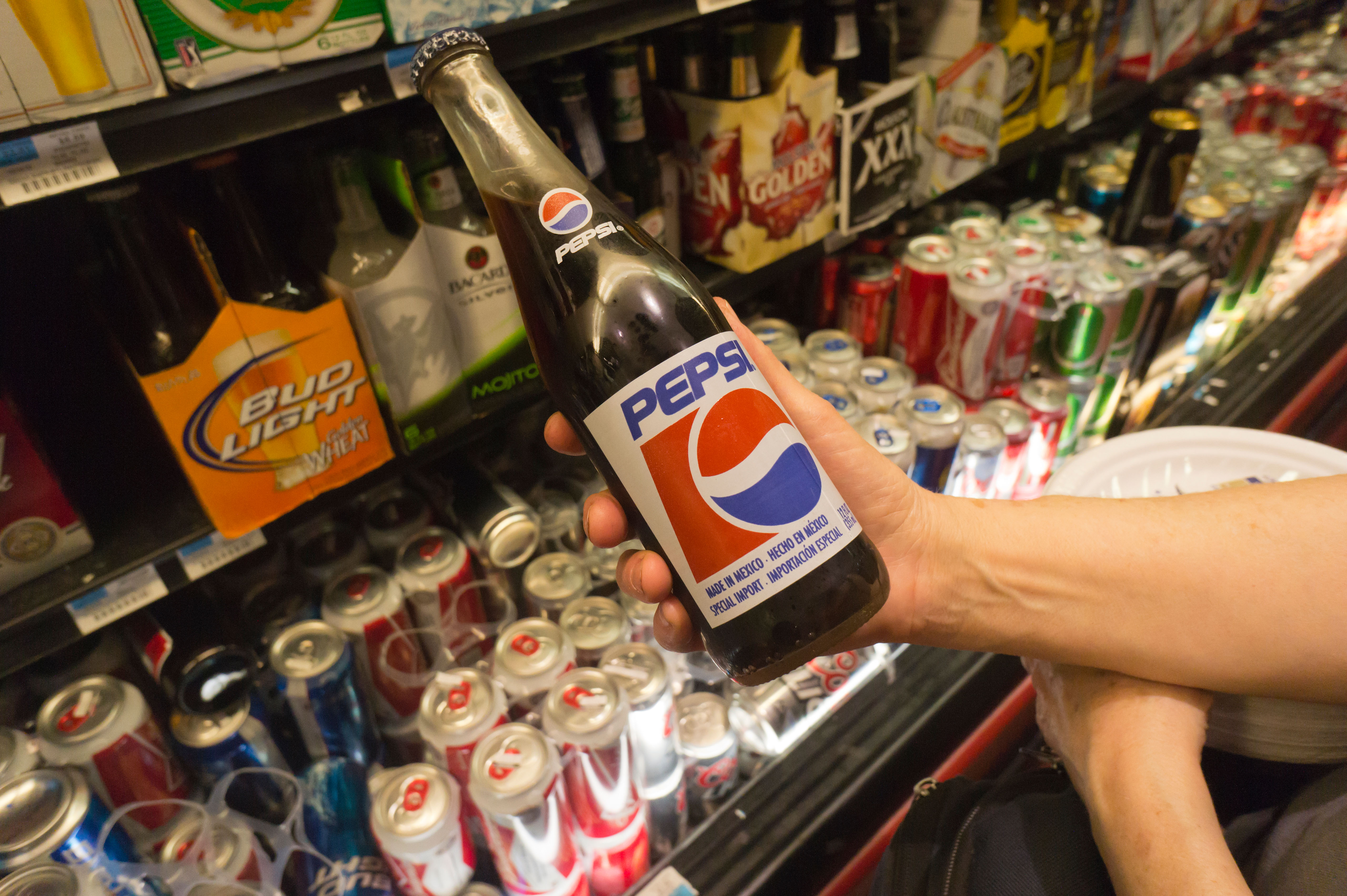 A customer contemplates the purchase of a glass bottle of Pepsi, made in Mexico, in a supermarket in New York.