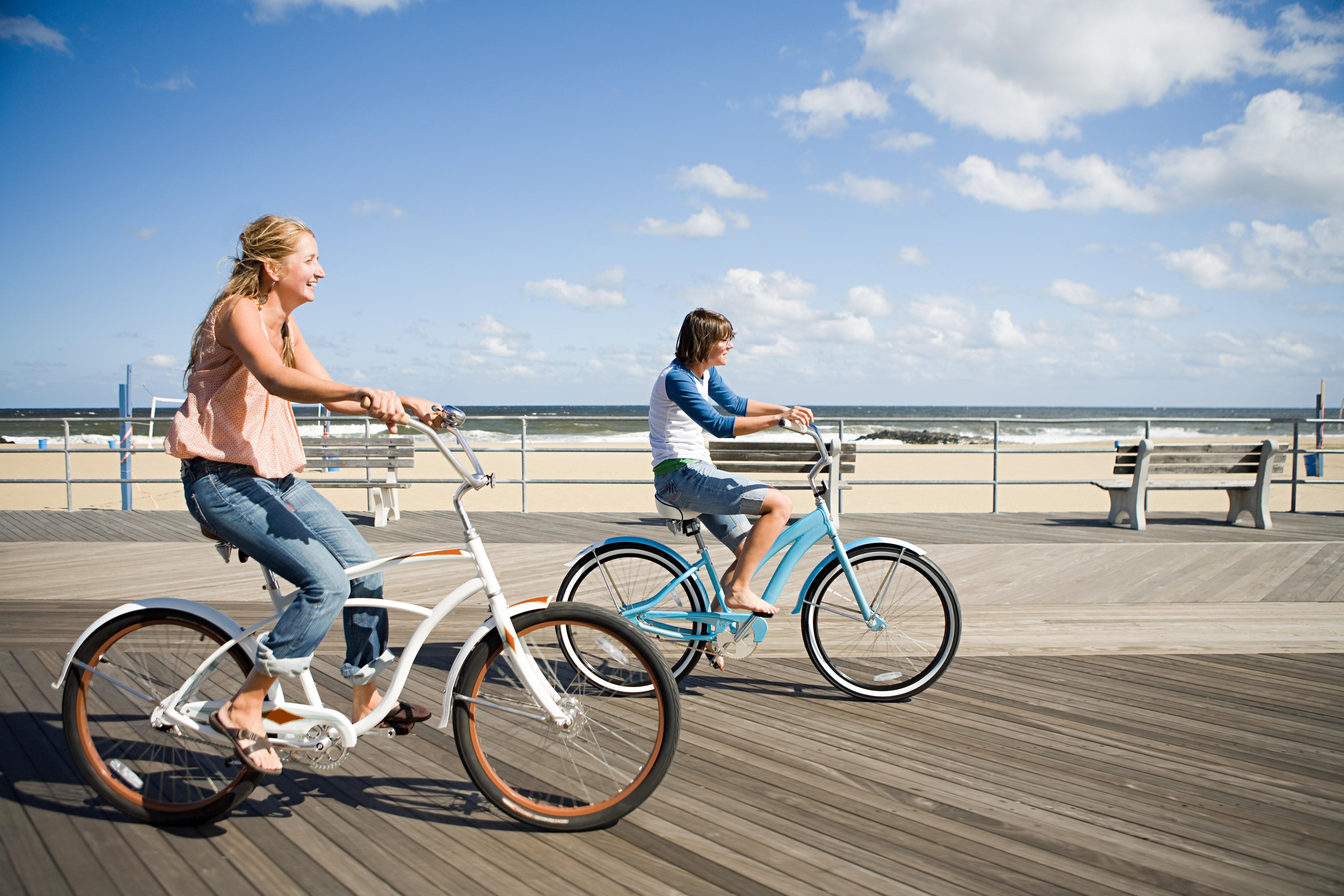 Two women cycling on boardwalk, Asbury Park, NJ