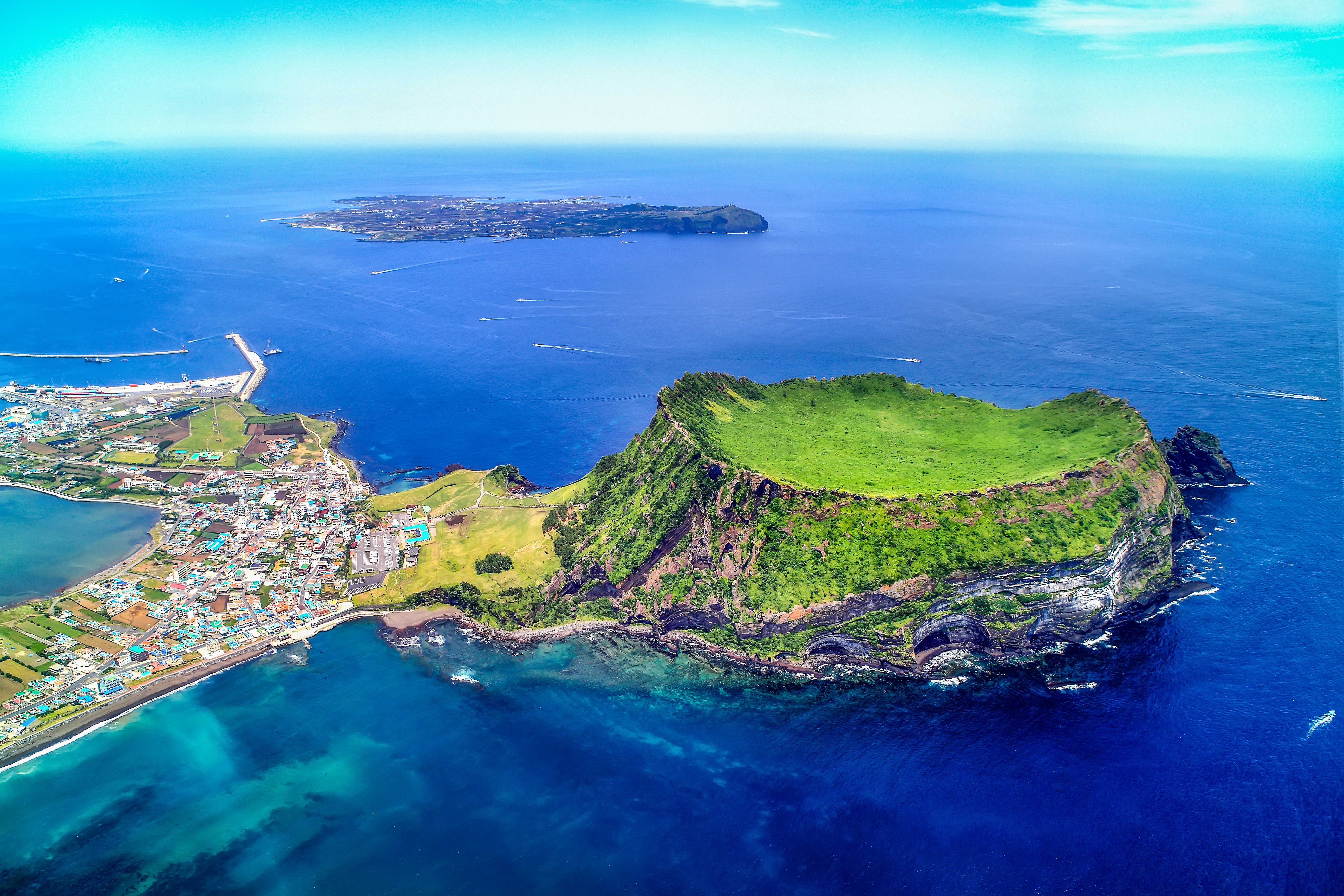 Aerial view of Seongsanilchulbong Cliff (Korea Natural Monument 420, UNESCO World Heritage Site) and Udo Island (Famous travel destination) in Jeju Island