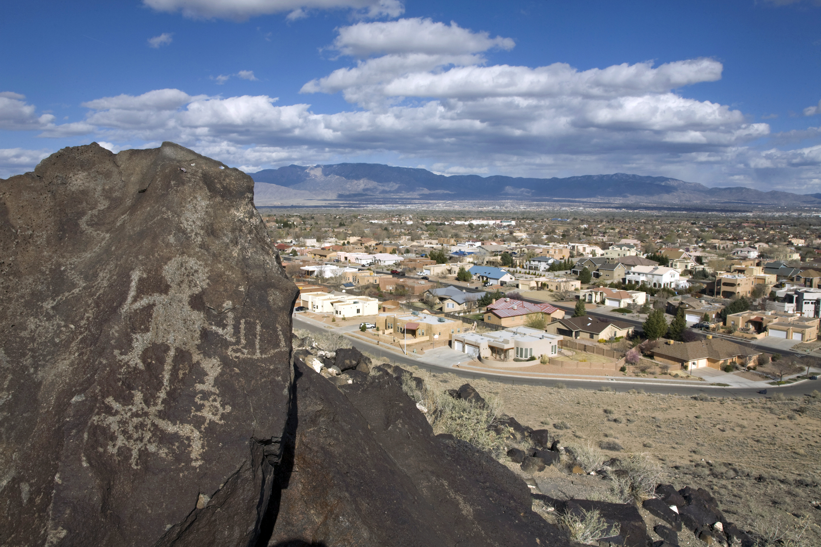 Prehistoric petroglyphs and heavy urbanization in the background.