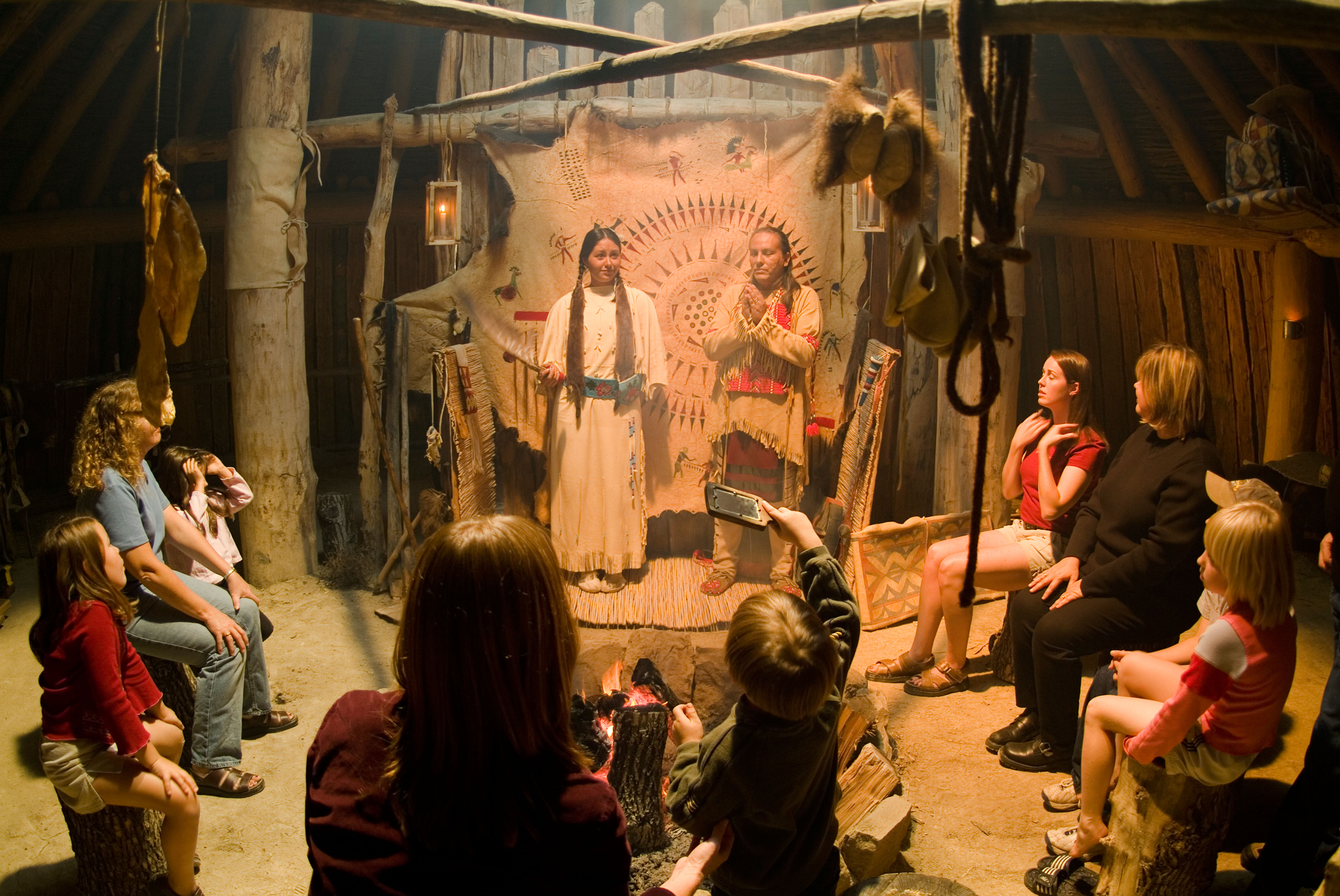 Native American Indians in an Earth Lodge at the On A Slant Village at Fort Abraham Lincoln State Park North Dakota