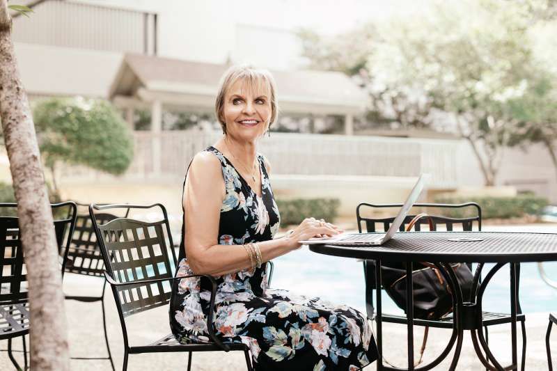 Carol Marak works poolside at her home in Dallas, Texas.