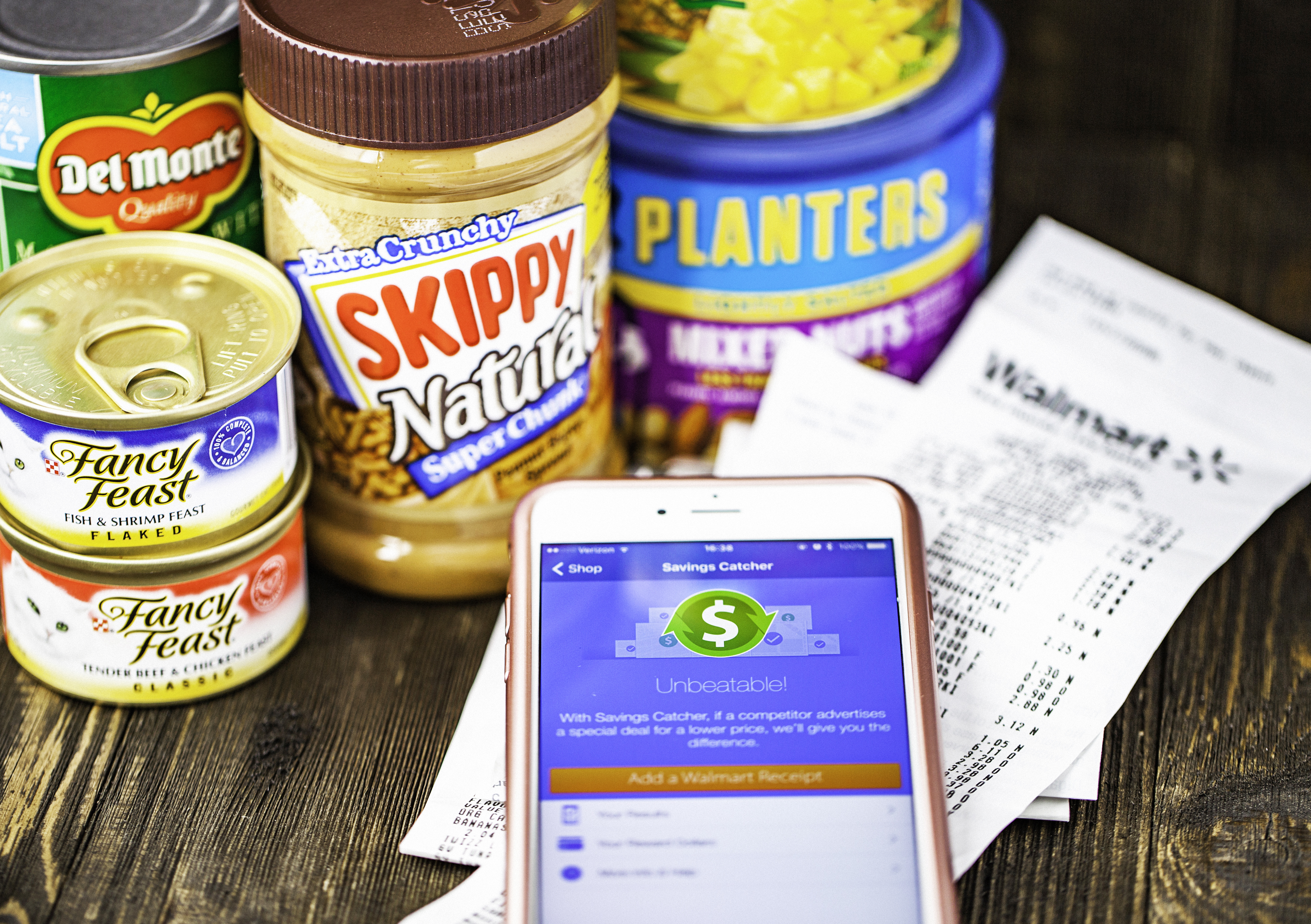 Walmart Savings Catcher App on iPhone screen and assorted groceries