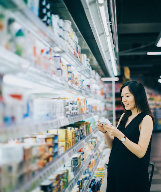 Asian pregnant woman grocery shopping in supermarket and reading nutrition label on a packet of cheese