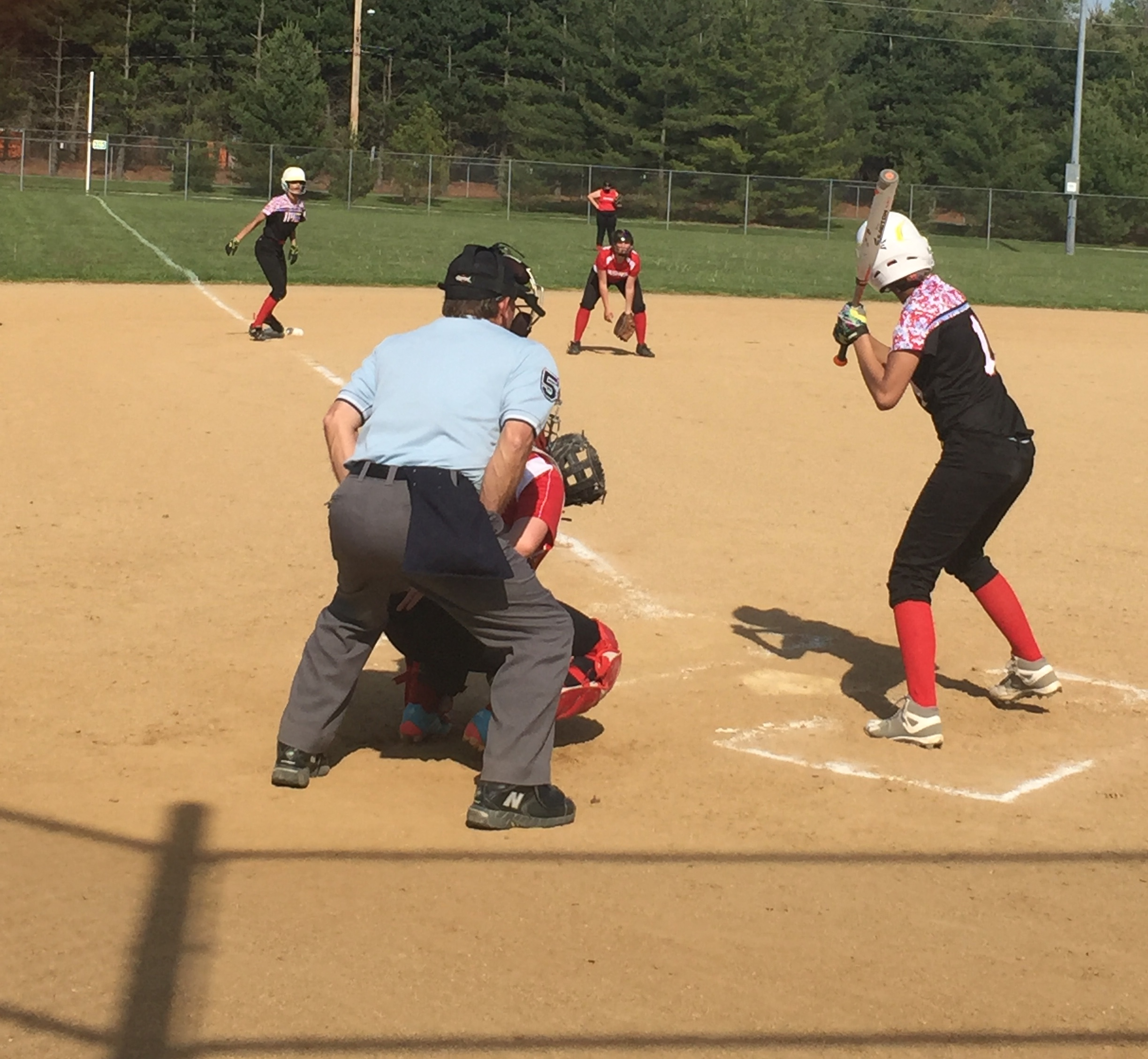 Angelica Malone at bat, trying to bring her older sister Christiana (on third base) home during a softball game last spring.