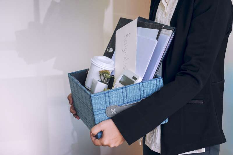 Midsection Of Employee Leaving The Office While Carrying The Box