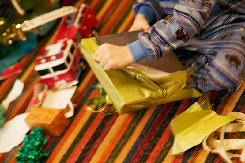 Young boy unwrapping Christmas present