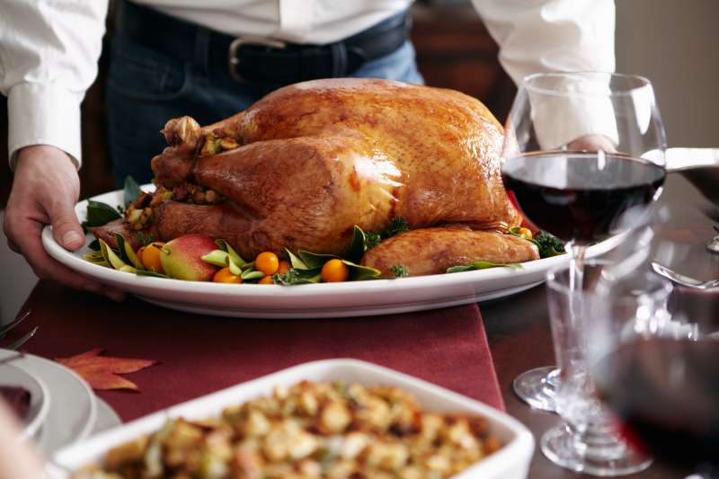Man serving turkey dish at table
