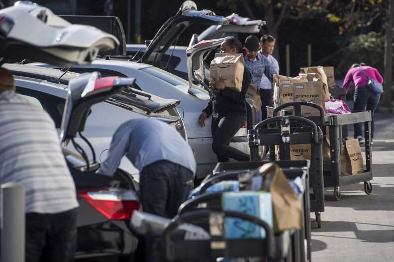 Contractors working for the Amazon Inc. Flex program load packages into vehicles to deliver to customers in San Francisco, California, on Oct. 30, 2018.