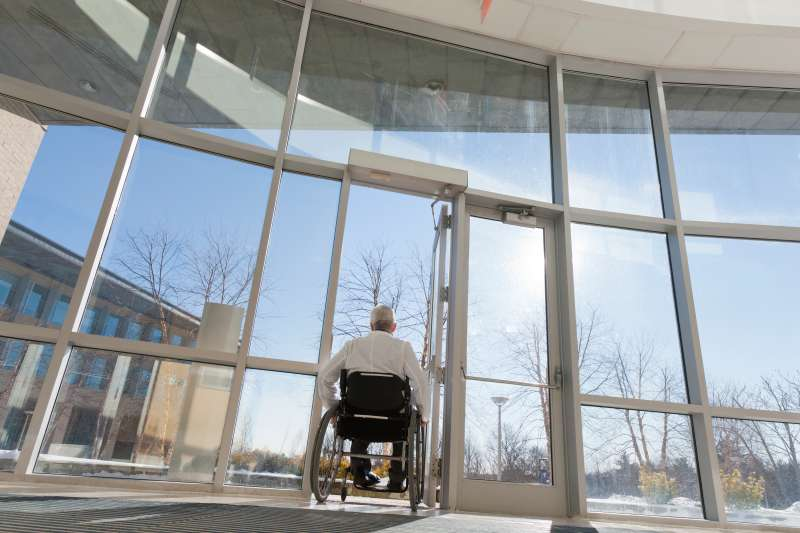 Doctor with muscular dystrophy in wheelchair leaving hospital entrance