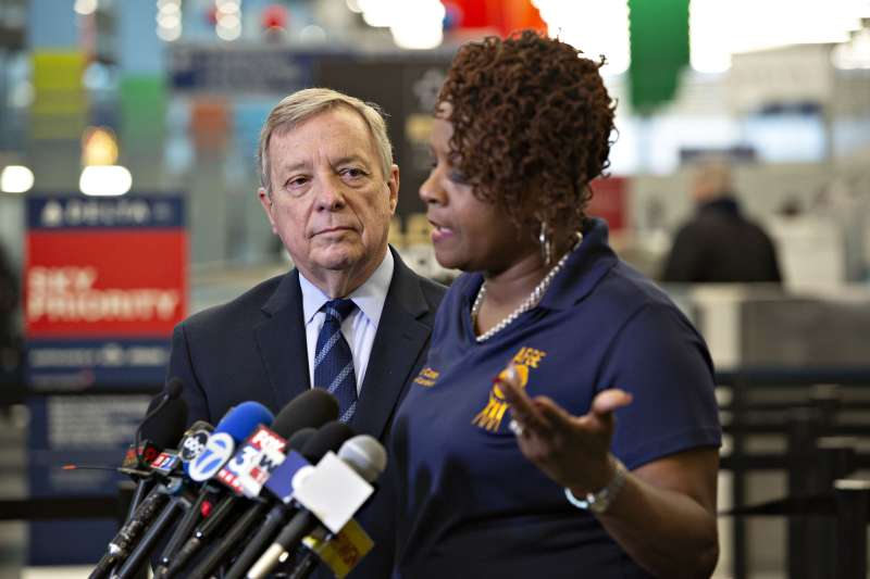 Janis Casey, women's coordinator for American Federation of Government Employees (AFGE), speaks while Senate Minority Whip Dick Durbin, a Democrat from Illinois, left, listens during a press conference on how the partial government shutdown is affecting Transportation Security Administration (TSA) employees at O'Hare International Airport (ORD) in Chicago, Illinois, U.S., on Tuesday, Jan. 8, 2019. With screeners already calling in sick in larger-than-normal numbers, U.S. airports are girding for disruptions next week if the partial government shutdown continues andTSA officers miss their first paycheck.