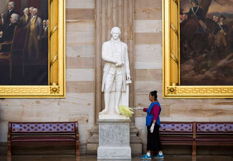 Maria Bernal de Navarrette cleans a statue of Alexander Hamilton, a Founding Father of the United States, in Rotunda on Capitol Hill in Washington October 15, 2013.
