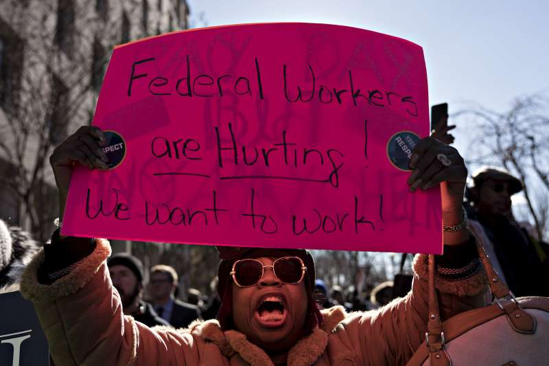 A furloughed federal employee holds a sign during a rally to end the partial government shutdown outside the American Federation of Labor & Congress of Industrial Organizations (AFL-CIO) headquarters in Washington, D.C., U.S., on Thursday, Jan. 10, 2019.