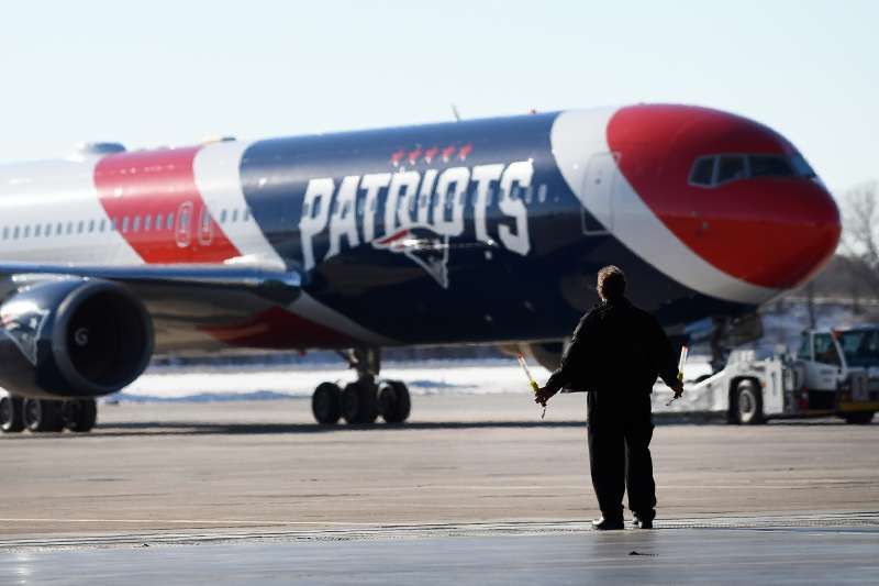 A member of the ground crew guides the team plane of the New England Patriots as it arrives for Super Bowl LII on January 29, 2018 at the Minneapolis-St. Paul International Airport in Minneapolis, MN.