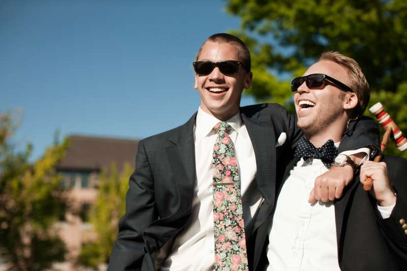 Laughing men hugging and holding croquet mallet