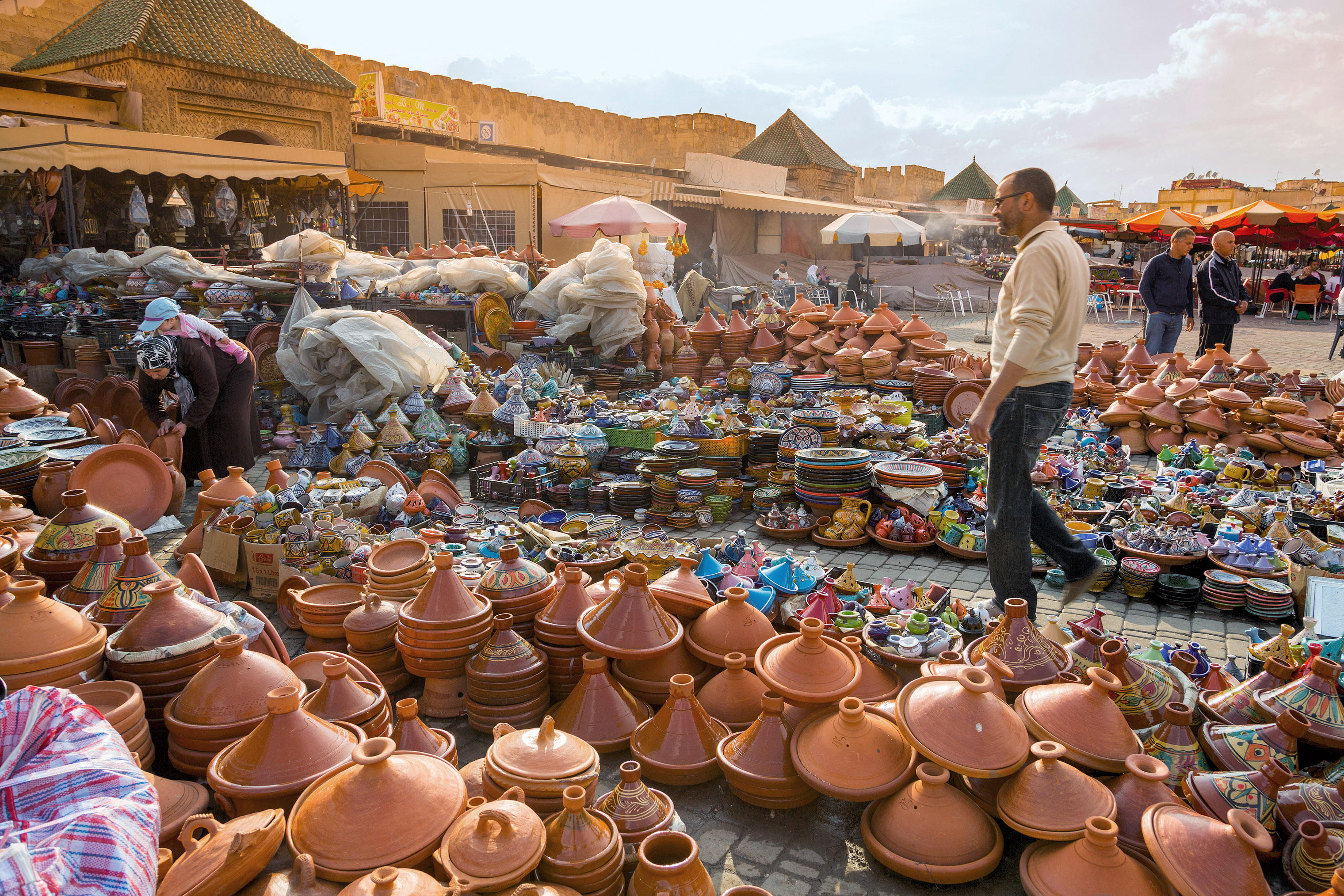 Traditional tagine pots are sold in the Meknes souks (left); ancient mosaics decorate the nearby ruins of Volubilis.