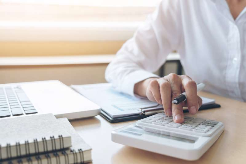Midsection Of Businesswoman Using Calculator At Desk In Office