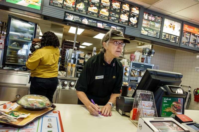 Senior woman working in McDonald's fast food restaurant.