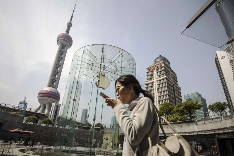 A woman using a smartphone walks past an Apple Inc. store in Shanghai.