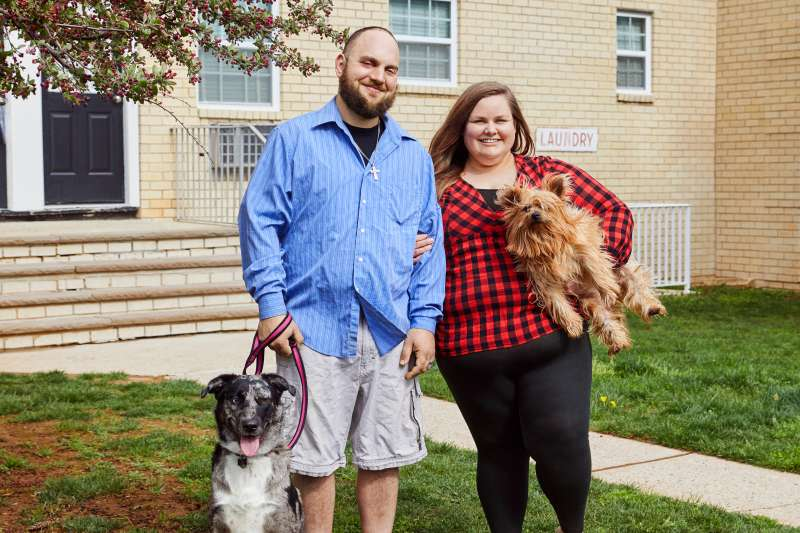 susskinds standing outside an apartment building with their two dogs