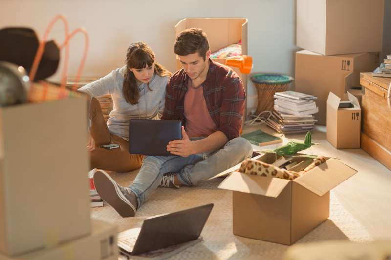 Young couple using laptop surrounded by moving boxes