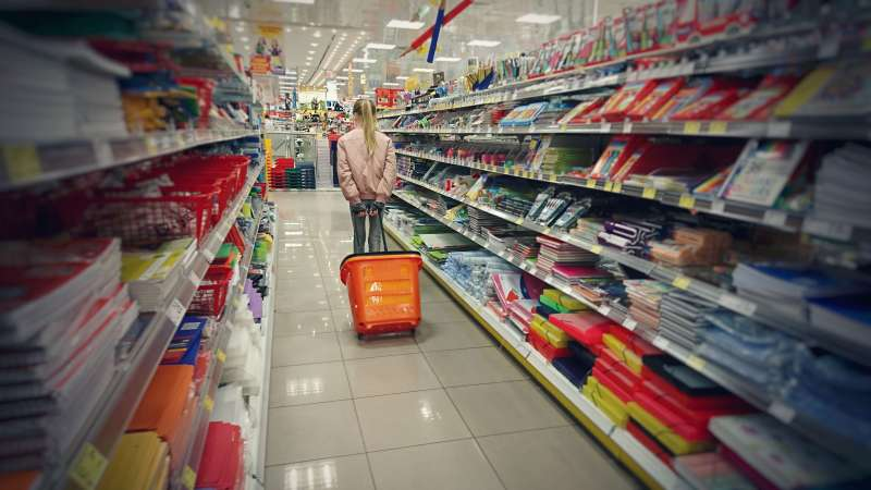 Child walking down the aisle of a shop selling 'back to school' stationery
