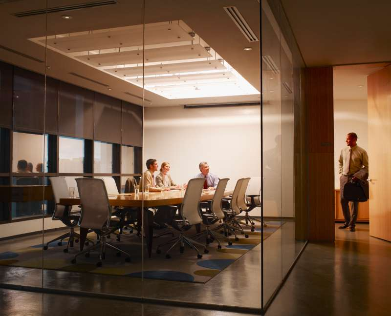 Three businesspeople in boardroom watching businessman leave