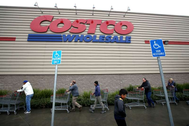 Customers wait in line to enter a Costco store on March 14, 2020 in Novato, California.