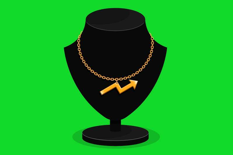 Black necklace stand bears a gold necklace with a golden arrow pendant