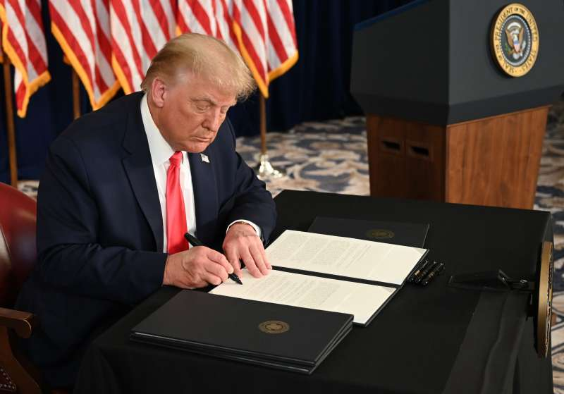 US President Donald Trump signs executive orders extending coronavirus economic relief, during a news conference in Bedminster, New Jersey, on August 8, 2020.
