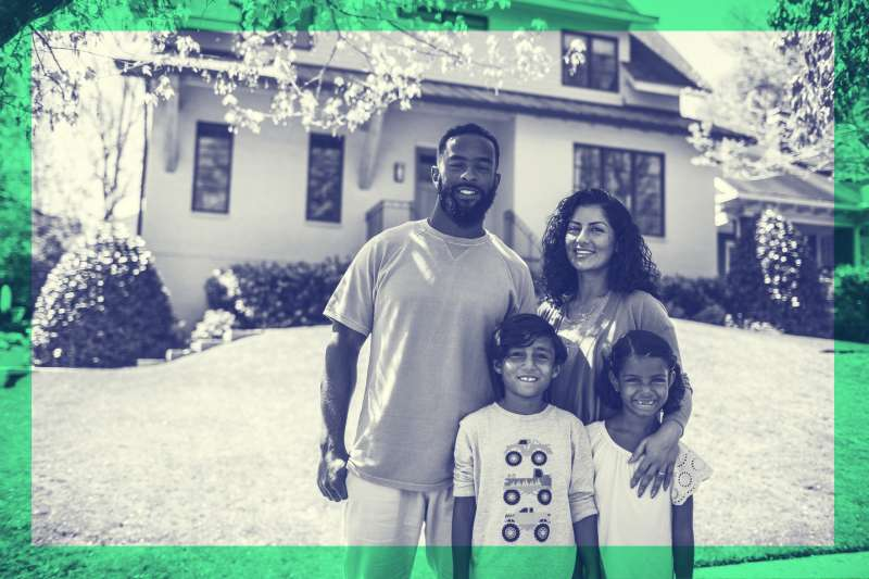 Black and white photo of family of four in front of house