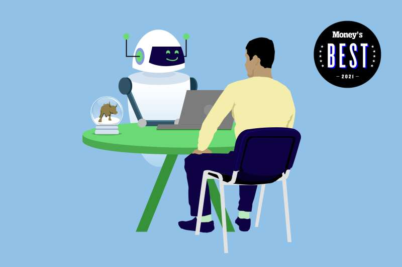 A man sits across a smiling robot using a laptop, there is a snow globe with a bull inside on the table