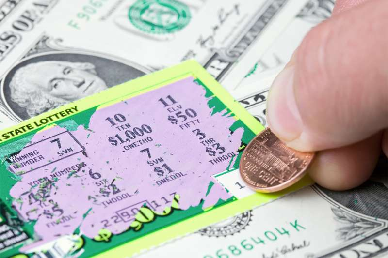 ottery player has scratched a winning ticket which rests on a dollar bill background.