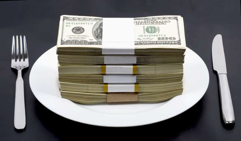 Stack of wrapped bills on top of a dinner plate with a fork and a knife on either side