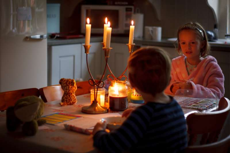 Young boy and girl sitting at the table eating breakfast by candle light.