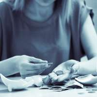 Woman counting money from her broken piggy bank