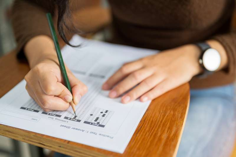 Woman sitting at a desk filling out a test answer sheet