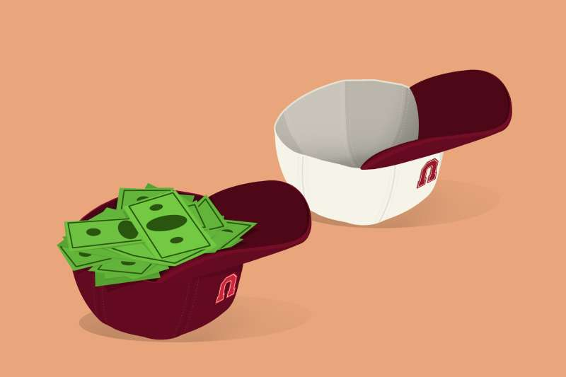 Two baseball caps upside down, one fills with cash and one without.