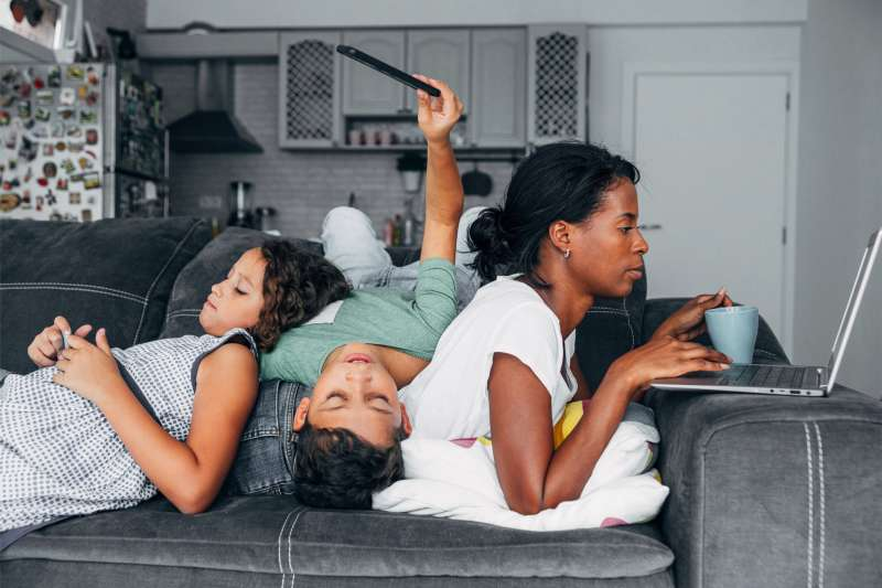 Mother and two kids sitting on the sofa at home using digital devices.