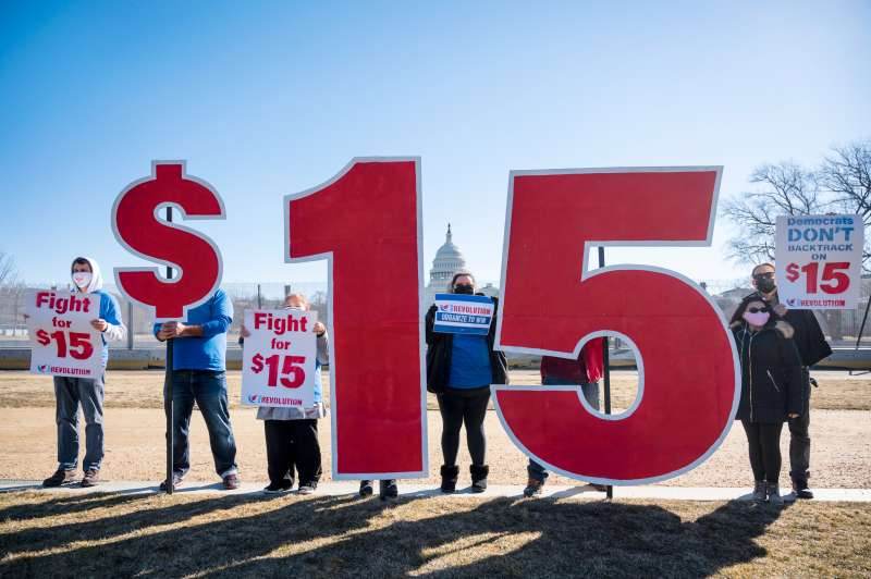 Activists with $15 minimum wage signs outside the Capitol