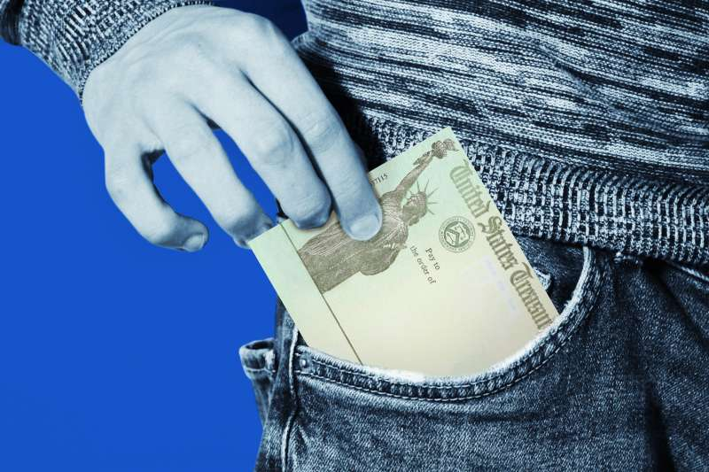 Person tacking out a stimulus check from their jean pocket