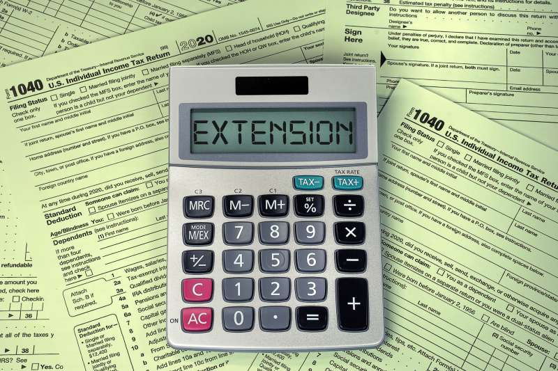Calculator with the word extension on top of multiple 1040 tax forms
