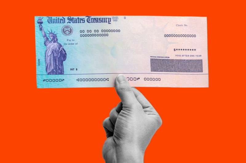 Photograph of a hand holding a United States Treasury Check on a colored background