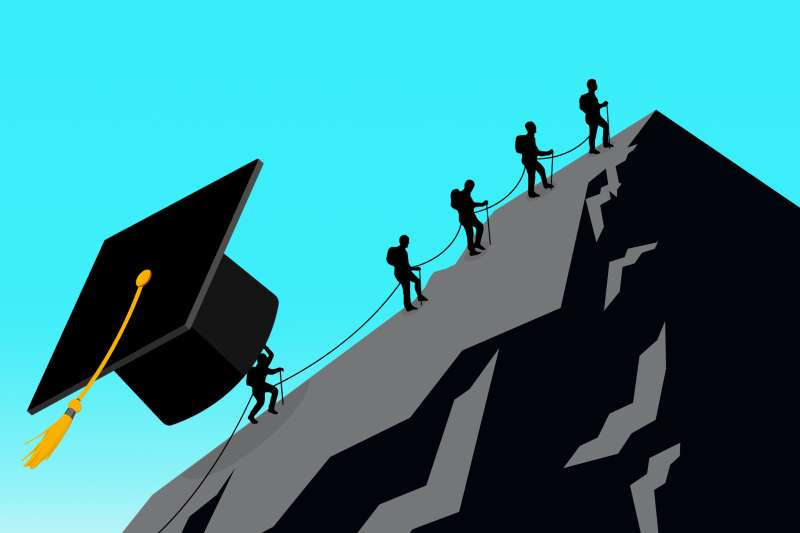 A group of people climbing a mountain, but the last person is further behind because s/he is holding a gigantic graduation cap.