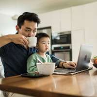 Father with young son on his lap while he looks at his computer at the kitchen table