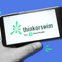 Hand holding a phone with the Think or Swim app open over a colored background