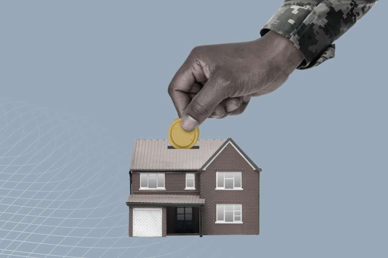Hand Of An Army Soldier Placing Coin Inside A Small House Shaped Piggy Bank